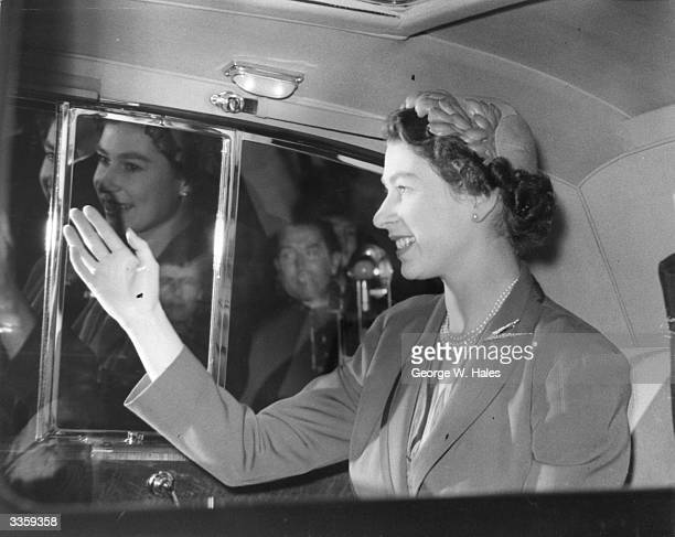 Queen Elizabeth II waving to crowds from a specially illuminated car en route to London Airport where she will board the Stratocruiser Canopus to...