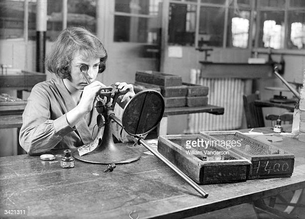 Worker at Messrs Gowllands in Croydon marking the exact centre point of optical lenses so that subsequent cuts will remain accurate.
