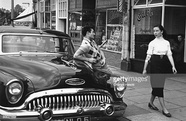 A man leaning on his American Buick car trying to draw the attention of a young woman passing by Original Publication Picture Post 7351 Which Came...