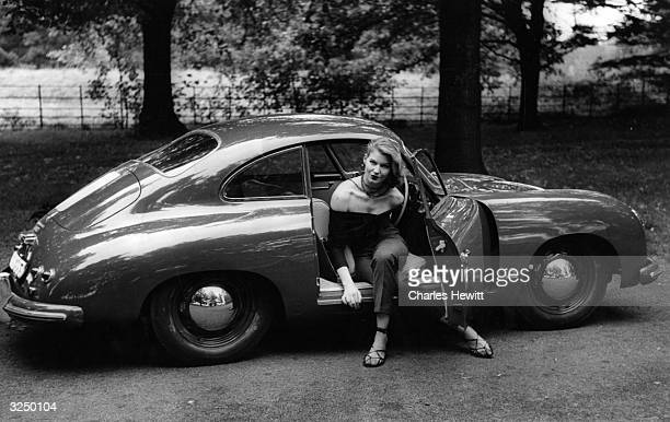 A Porsche being demonstrated by a young model Original Publication Picture Post 7351 Which Came First The Woman Or The Car pub 1954