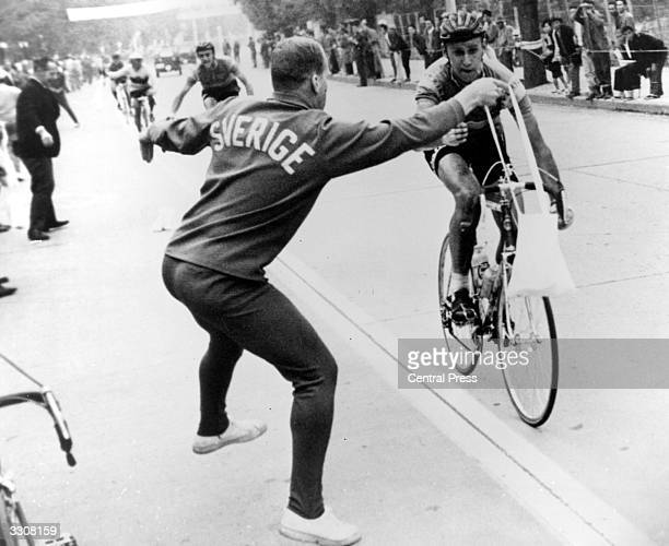 Swedish cyclist Gosta Peterson is handed his musette a bag of food by his trainer during the road race at Tokyo during the 18th Olympic Games