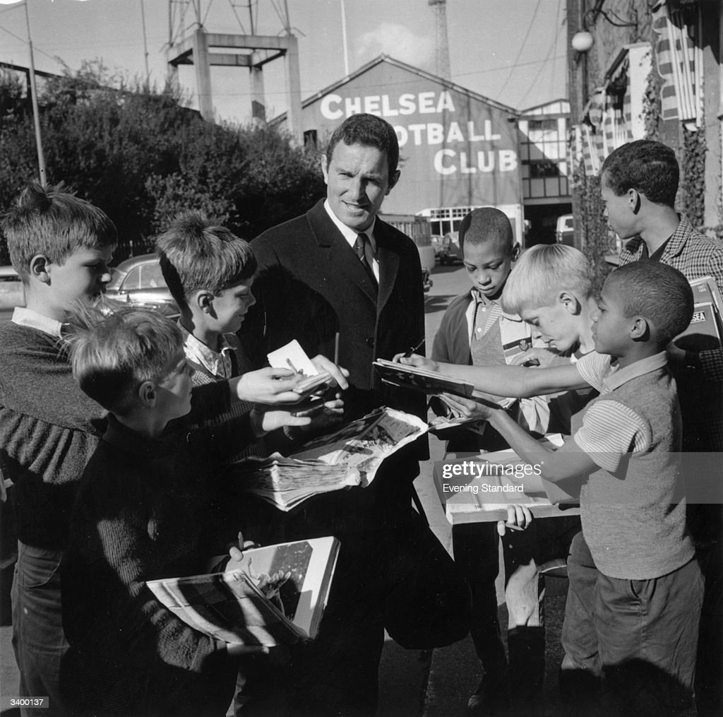 Chelsea manager Dave Sexton signs autographs for young fans outside the Chelsea ground at Stamford Bridge.