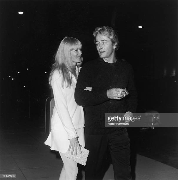 American film director and actor John Derek and his wife, American actor Linda Evans, walk together at the Daisy Club anniversary party. Derek holds...