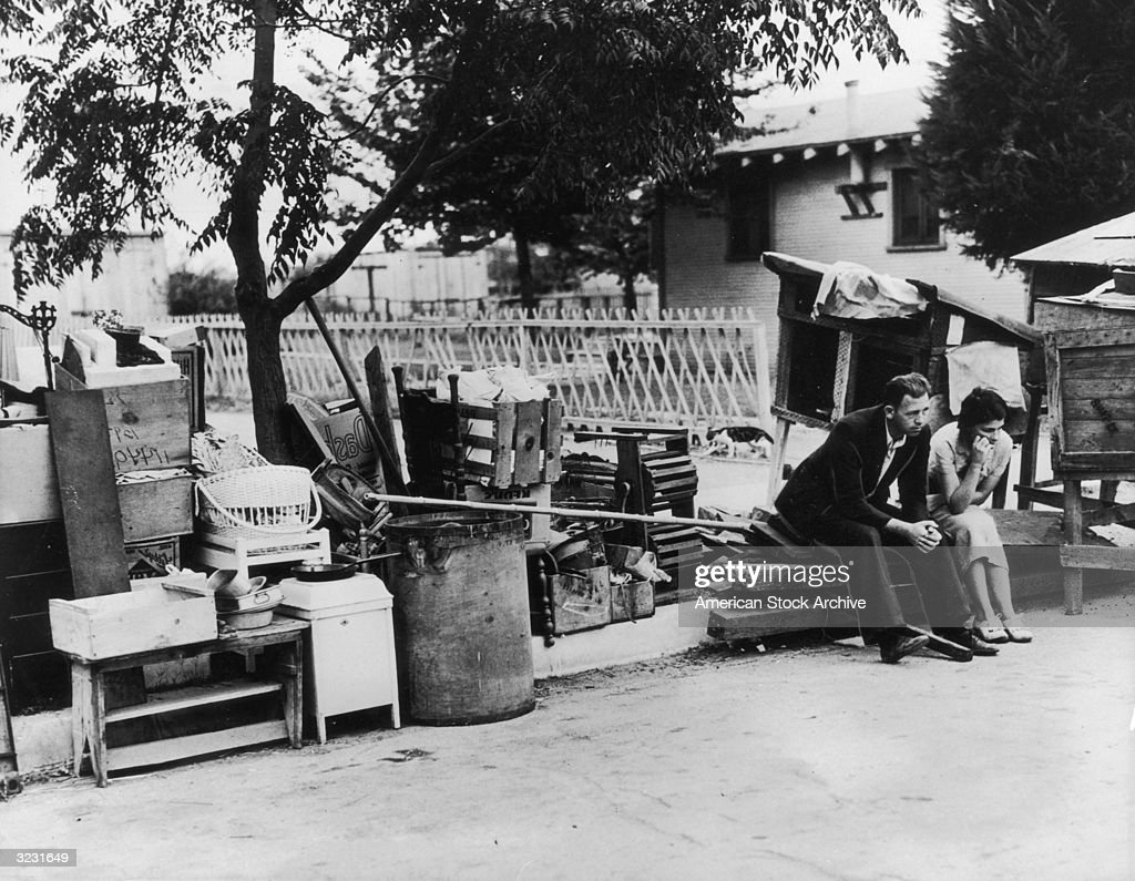 An evicted couple sits on the curb surrounded by their belongings during the Great Depression, Los Angeles, California.