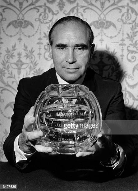 England Manager Alf Ramsey holds a Royal Brierley crystal football inscribed with the names of the 1966 World Cup winners