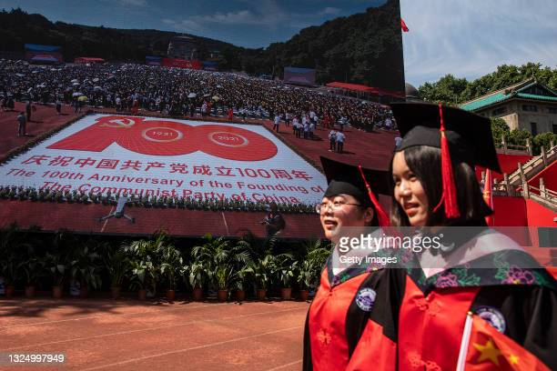 23th: Two graduate pass through the big screen shows the centenary of the founding of the CPC in Wuhan University on June 23, 2021 in Wuhan, China....