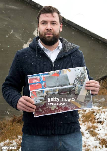A 23yearold man that does not want to be named holds up a photo of a destroyed garage during a press conference of the state office of criminal...