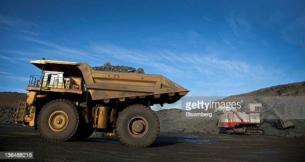 A 240ton capacity production truck left drives out of an open pit mine with a load of taconite heading to the taconite processing plant at the...