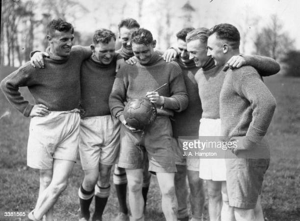 Huddersfield FC football team, Jackson autographing a football.