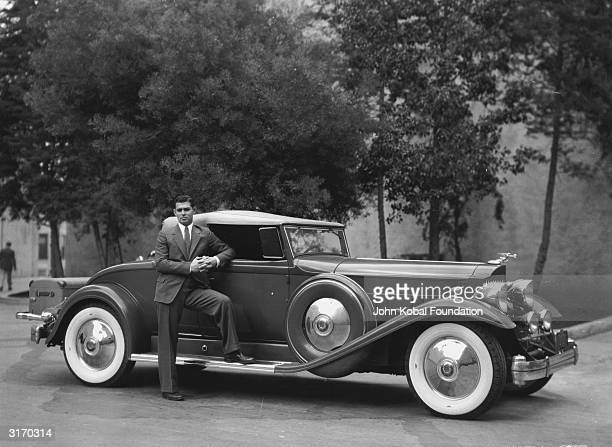 American screen star Clark Gable who became known as the 'King of Hollywood' poses next to his luxurious car with white walled tyres