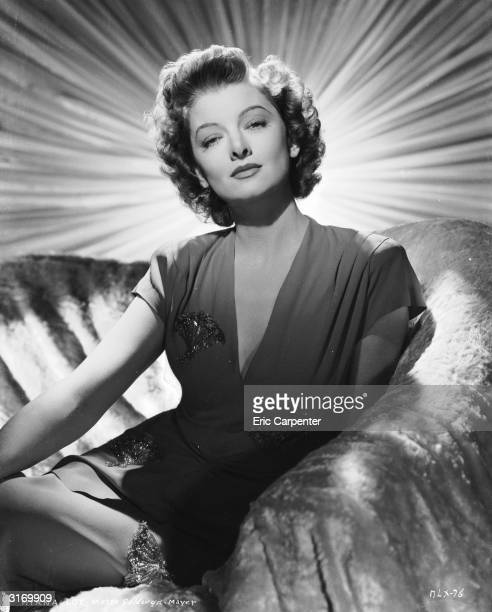 American actress Myrna Loy sitting on a covered sofa with a curtain with a bright sunshine design behind her