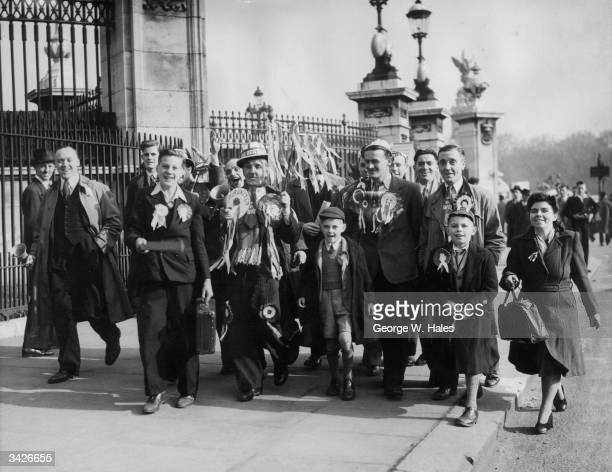 A group of Manchester United fans walk past the gates of Buckingham Palace on the morning of the FA Cup Final between Manchester United and Blackpool...