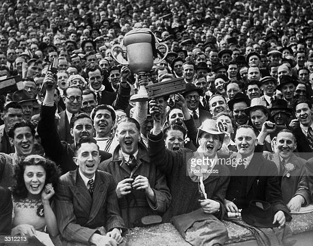 Football supporters at the FA Cup Final between Manchester United and Blackpool at Wembley London One of the crowd holds aloft a replica of the cup...