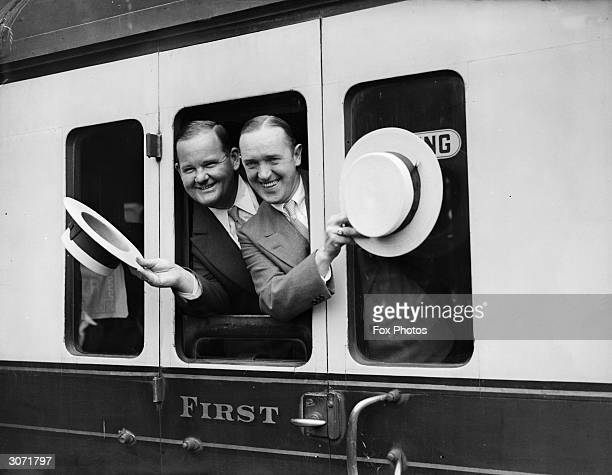 Comedy duo Stan Laurel and Oliver Hardy wave goodbye as their train pulls out of Paddington Station London en route to America