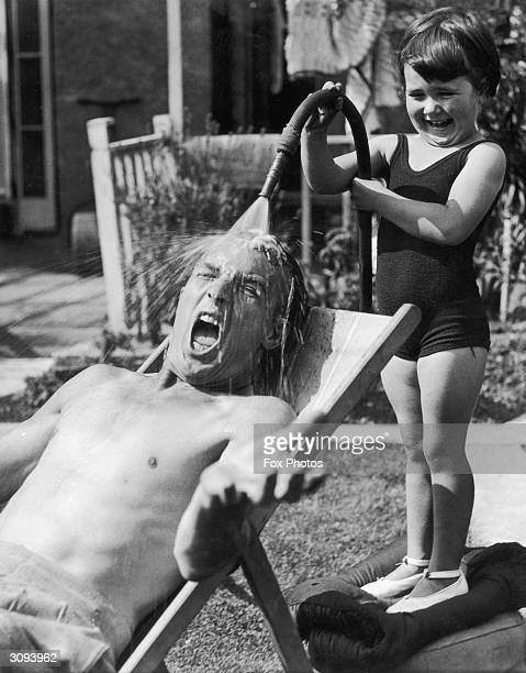 Little girl takes great delight in drenching her dad with shockingly cold water from the garden hose as he sunbathes on a hot day.