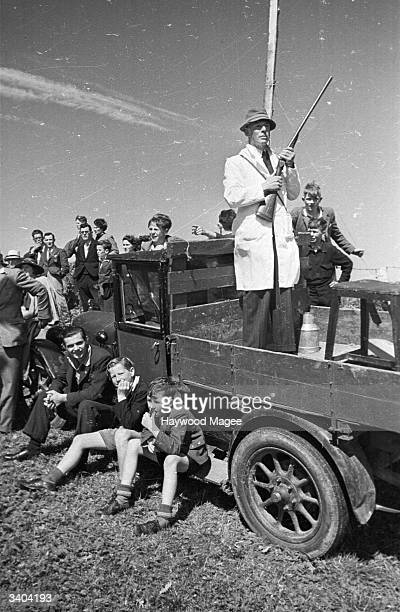 A steward about to fire a shotgun to start a race meeting in Newport South Wales Original Publication Picture Post 4193 Poor Man's Race Meeting pub...