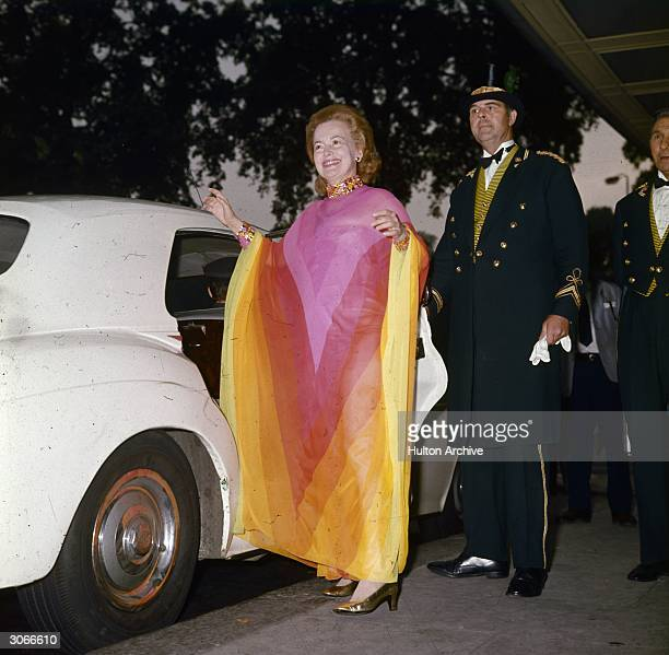 Aided by a doorman British actress Olivia De Havilland leaves the Dorchester Hotel in London for a dinner date with British prime minister Edward...