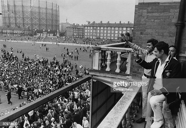 Indian skipper Ajit Wadekar and teammate B S Chandraserhar wave to cheering crowds at the Oval after India won the Test Series against England