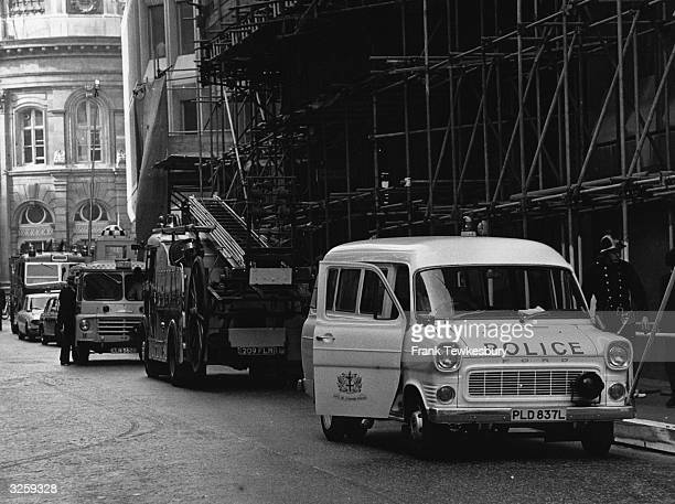 Police and fire engines parked at the scaffoldingcovered front entrance of the Stock Exchange London