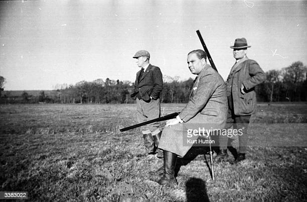 A hunter rests on his shooting stick a portable onelegged stool during a pheasant shoot in the English countryside Original Publication Picture Post...