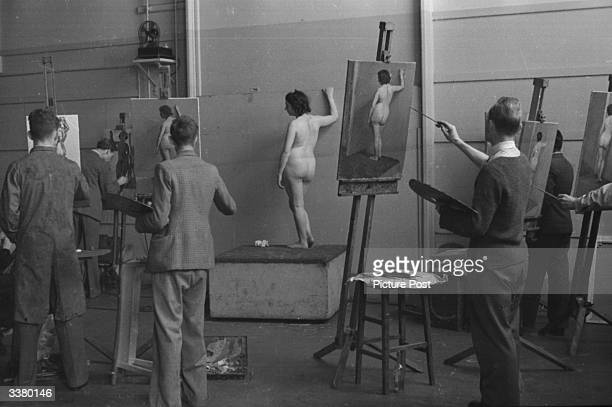 A group of male students painting a nude woman for a piece of work towards their Diploma at the Royal College Of Art they have been painting this...
