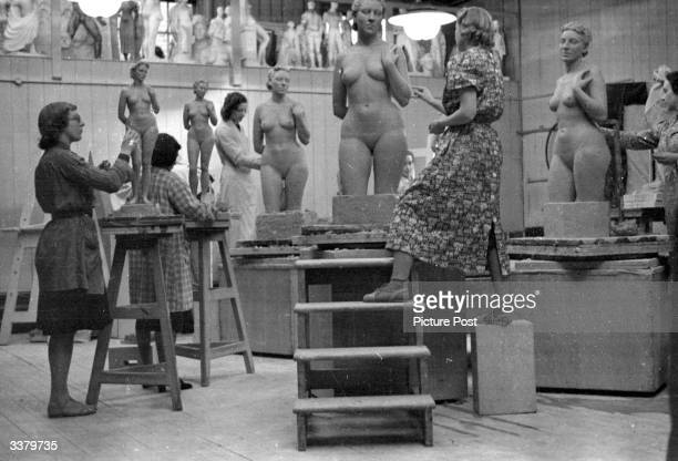 Group of students in a sculpture class working on a figure in modelling clay for their three year diploma course at the Royal College Of Art in...