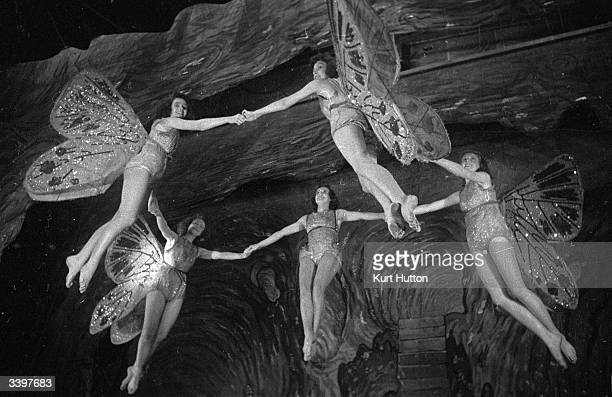 A group of actresses in the roles of Neverneverland fairies in a London stage production of 'Peter Pan' are hoisted aloft by Joseph Kirby's invisible...