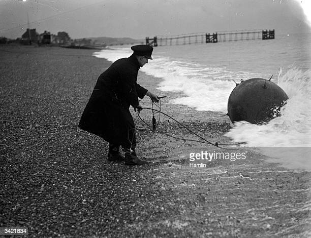 A bomb disposal officer gently pulling a mine from the sea on the South East coast of Britain near Hythe