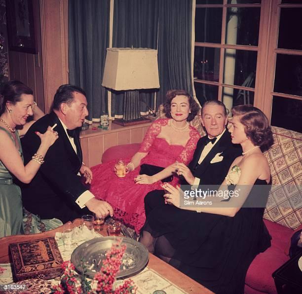 Christmas eve at the Bogart's house in Beverly Hills From l to r Kendall and Lewis Milestone Mrs Oscar Levant film star Clifton Webb and hostess...