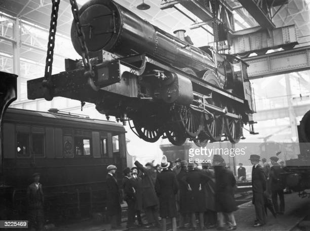 A group of Eton college students watching the 'star' class engine Knight Templar being lifted at GWR's Swindon works