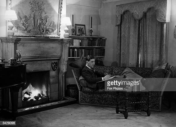 Couturier and court dressmaker Norman Hartnell at home by the fireside.