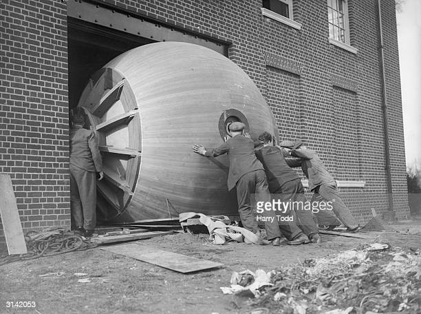 A sphere over 11 feet in diameter which is used for measuring the candle power of electric light is being manoeuvred with difficulty through a door...