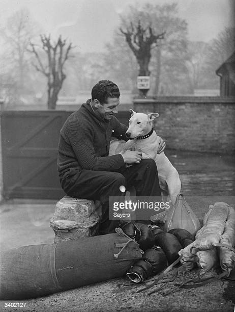 Len Harvey ex British and Empire heavyweight boxer makes friends with a bull terrier during a lull in training at Jack Straw's Castleon Hampstead...