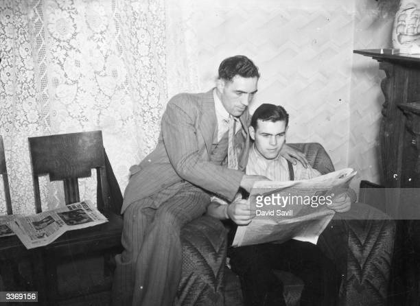 British boxer Arthur Danahar reading an account of his unsuccessful British lightweight title fight against Eric Boon the previous night. His brother...