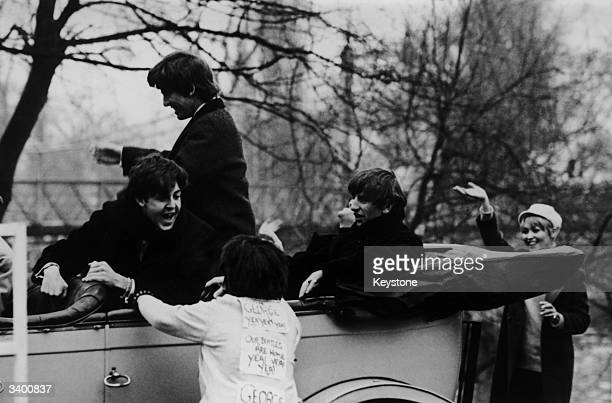 16 year old Susan Sims bedecked with signs celebrating the Beatles return from America runs to the 1912 Rolls Royce that is taking the Beatles from a...