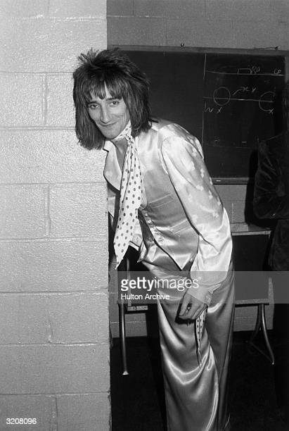 British rock singer Rod Stewart leans against a wall backstage at Madison Square Garden in New York City Stewart is wearing matching satin pants and...