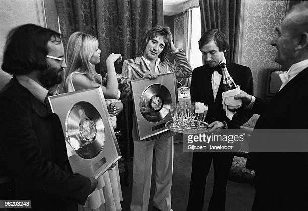 British musician Rod Stewart with his partner Britt Ekland pose with gold discs at a press conference to promote his LP 'Atlantic Crossing' in...
