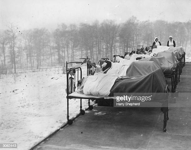 Patients crippled by tuberculosis are treated outdoors in the snow at the Harlow Wood Orthopaedic Hospital in Nottinghamshire. Whatever the weather,...