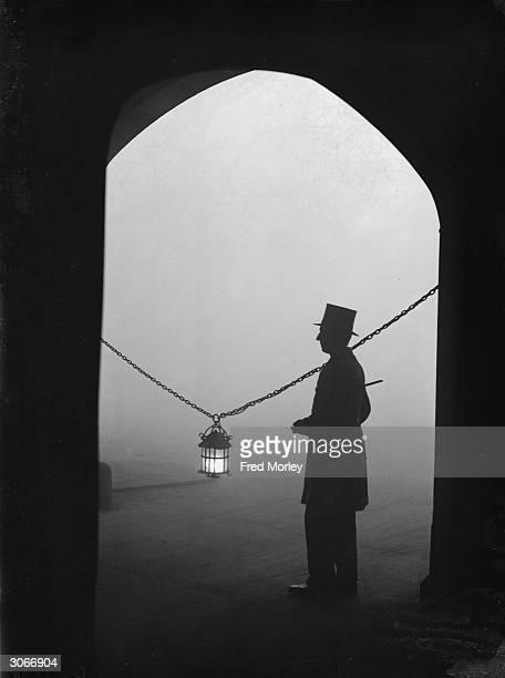 An eerie scene in Lincoln's Inn Fields, London, where a lantern helps to illuminate the way through a dense fog.