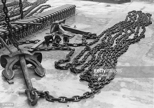 The world's largest anchor chain for the liner Majestic dwarfs dock workers at Southampton
