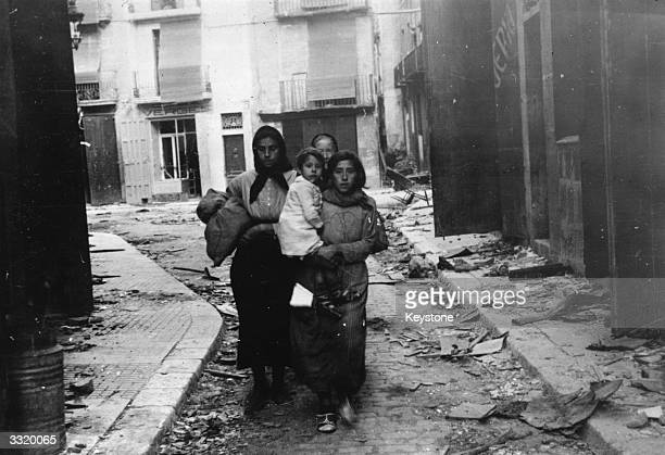 Women and children who fled when the Spanish Nationalist troops started bombarding Tortosa returning to their home to find it in ruins during the...
