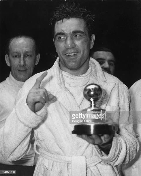 American boxer Joey Maxim with the light-heavyweight boxing trophy after he had knocked out Freddie Mills in the tenth round at Earl's Court.