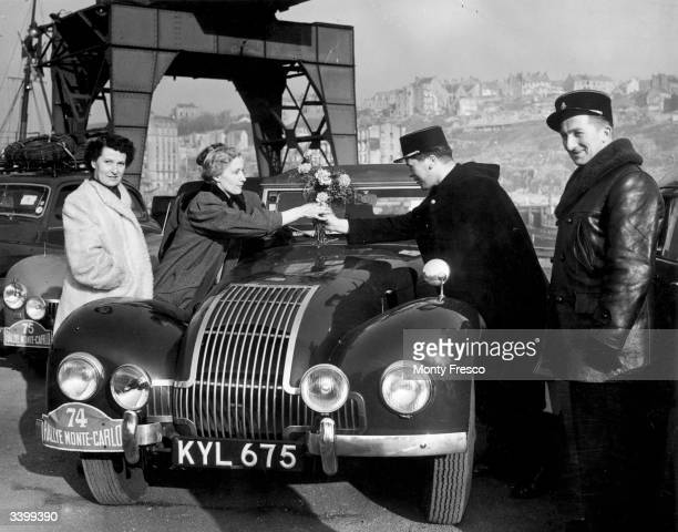 Mrs Eleanor Allard in her Allard car and a member of her all woman team being greeted with flowers by a gendarme on landing at Boulogne during the...