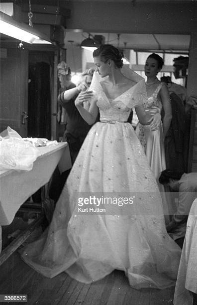 Arranging a model's dress, designed by couturier Sir Norman Hartnell. Original Publication: Picture Post - 6392 - Hartnell And The Coronation - pub....