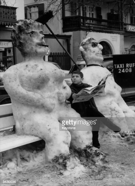 A boy sitting between a giant snowman and snowwoman in a street in GarmischPartenkirchen Bavaria