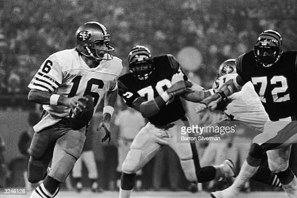 San Francisco 49ers quarterback Joe Montana runs past two Cincinnati Bengals players while looking for a receiver in Super Bowl XVI at the Pontiac...