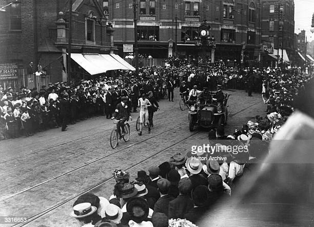 Competitor in the Marathon at the 1908 London Olympics, surrounded by accompanying bicycles and a car, and watched by a large crowd in Harlesden,...