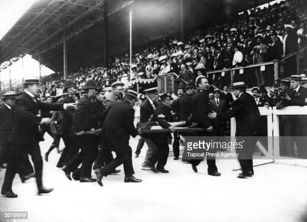 Dorando Pietri of Italy is stretchered away after collapsing in the Marathon at the 1908 London Olympics. Despite finishing first, he was...