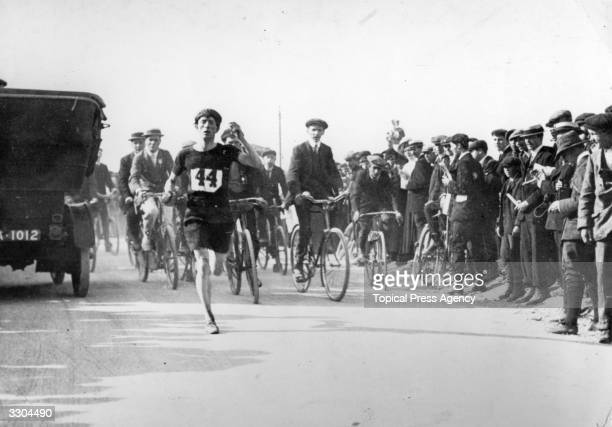 Gardiner, one of the competitors in the Marathon at the 1908 London Olympics pursued by a group of cyclists and watched by a group of spectators on...