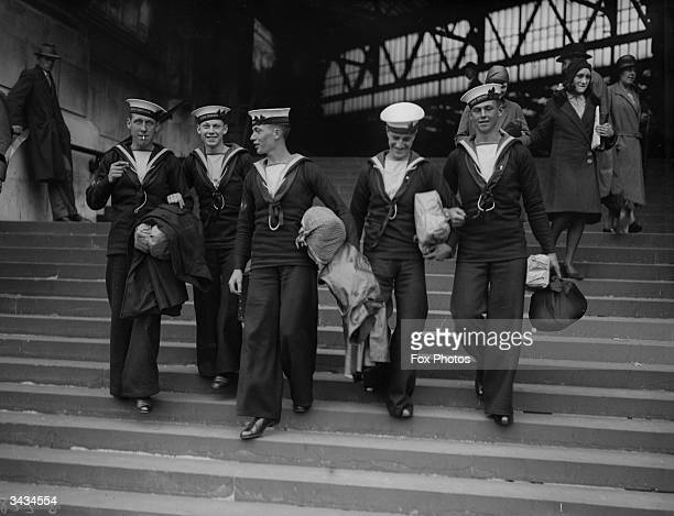 Coming down a station's steps, sailors going home on leave